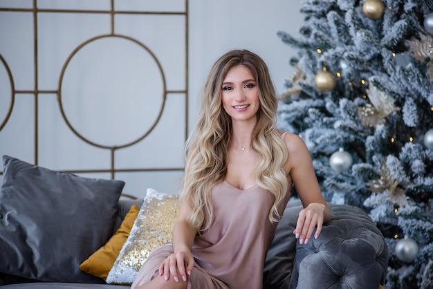 Belle fille blonde bouclée est assise sur un canapé gris, son sourire aux dents blanches sur l'arbre de noël