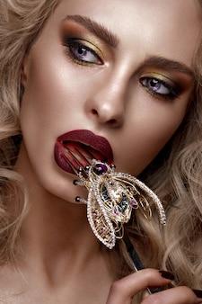 Belle fille blonde avec des boucles, du maquillage lumineux et des accessoires de créateurs