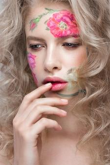 Belle fille blonde avec des boucles et un motif floral sur le visage. fleurs de beauté.