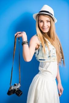 Belle fille blonde branchée avec appareil photo vintage pose.
