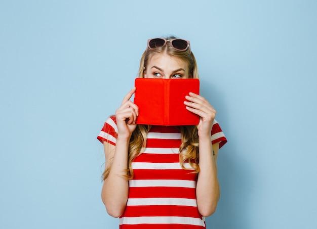 Belle fille blonde cachant ses yeux avec un carton rouge sur un fond bleu