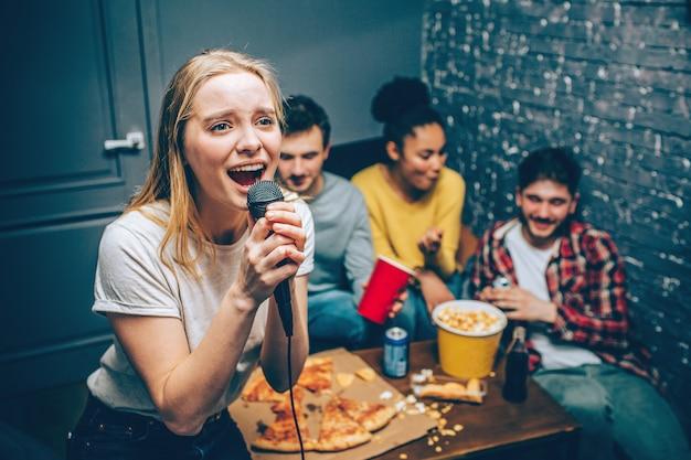 Belle fille blonde chante une chanson au microphone