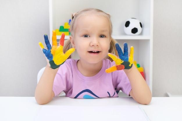 Belle fille blonde avec des couleurs peintes sur ses mains, souriant joyeusement