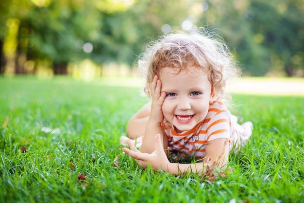 Belle fille blonde curle dehors dans un champ avec la lumière du soleil sur ses cheveux