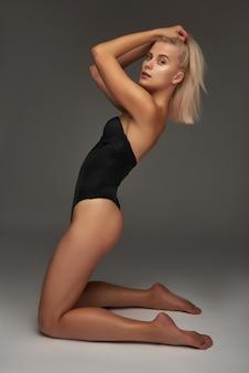 Belle fille blonde dans un body noir en studio