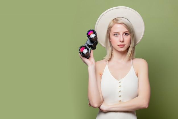 Belle fille blonde dans un chapeau blanc et une robe avec des jumelles