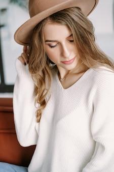 Une belle fille blonde dans un chapeau est assise sur un canapé marron
