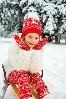 Belle fille blonde dans un chapeau rouge et des mitaines tricotées est assise dans un traîneau contre le parc enneigé