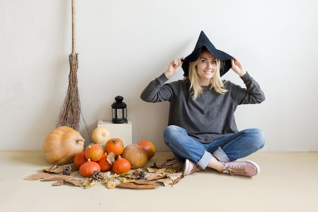 Belle fille blonde dans un chapeau de sorcière avec citrouilles et un balai sur blanc