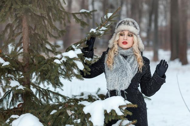 Belle fille blonde dans la forêt d'hiver se tient près d'un arbre
