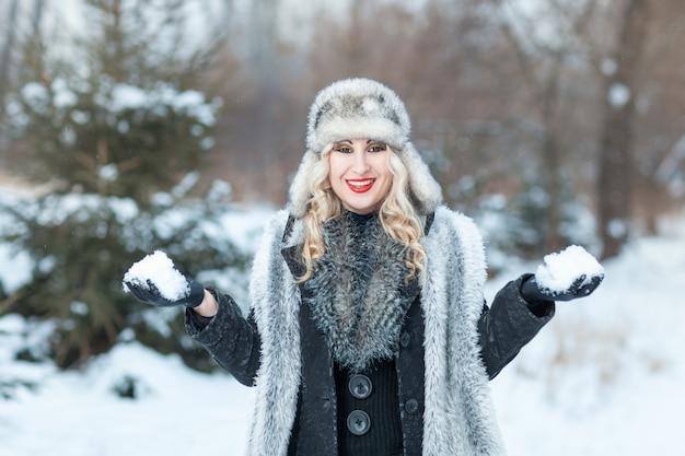 Belle fille blonde dans la forêt d'hiver tenant des boules de neige