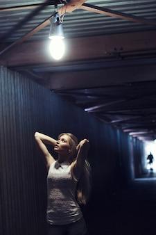 Belle fille blonde dans un tunnel piétonnier
