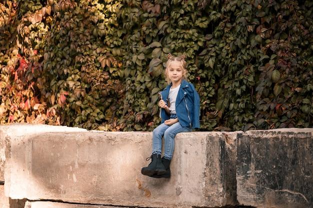 Une belle fille blonde élégante dans une veste bleue est assise sur un bloc de béton. fille 7 ans avec un sourire sur un fond de feuilles