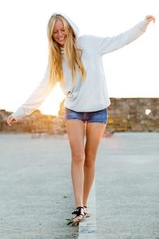 Belle fille blonde équilibrée sur un trottoir dans la ville.