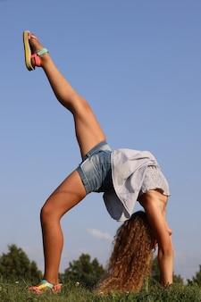 Belle fille blonde fait un pont d'exercice de gymnastique dans la nature. photo de haute qualité
