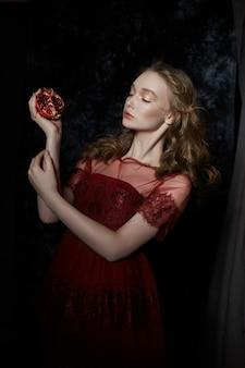 Belle fille blonde avec des fruits de grenade dans ses mains. portrait de printemps d'une fille en robe rouge brisant une grenade, du jus coulant dans ses mains