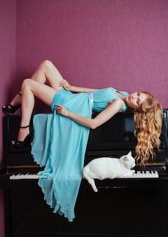 Belle fille blonde jouant du piano avec un chat