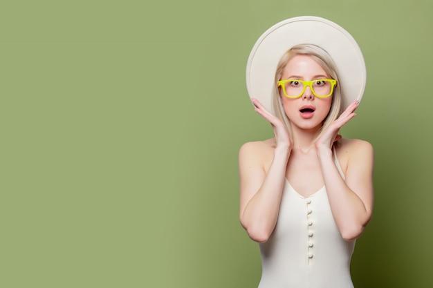 Belle fille blonde à lunettes et chapeau blanc