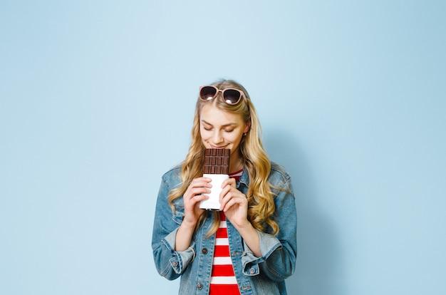 Belle fille blonde, manger du chocolat est excitée sur fond bleu