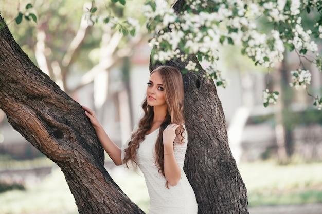 Belle fille blonde marchant dans un parc de printemps. femme lumineuse, jardin printanier