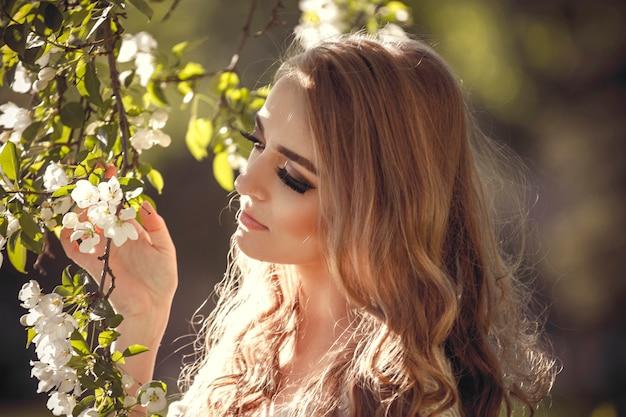 Belle fille blonde marchant dans un parc de printemps