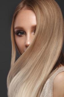 Belle fille blonde en mouvement avec des cheveux parfaitement lisses et un maquillage classique