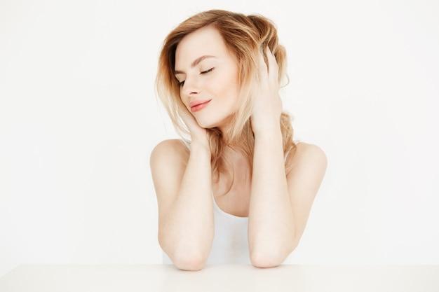 Belle fille blonde avec une peau propre et fraîche, assis à table, toucher les cheveux en souriant. beauté de la peau et spa. yeux fermés.