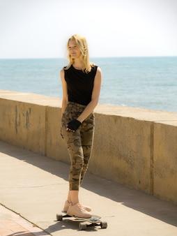 Une belle fille blonde sur planche à roulettes en journée chaude d'été sur le front de mer. planche à roulettes joyeuse fille