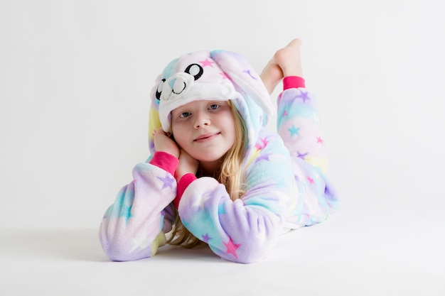 Belle fille blonde posant sur blanc en pyjama kigurumi, costume de lapin