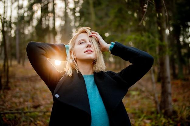 Belle fille blonde en pull bleu dans une forêt