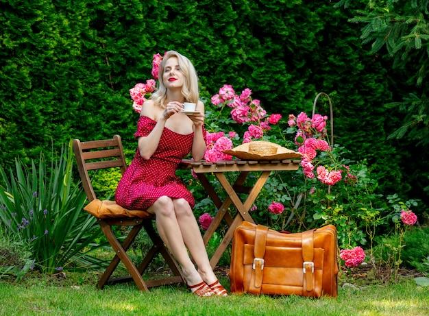 Belle fille blonde en robe rouge avec valise boit un café dans un jardin