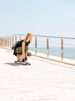 Une belle fille blonde avec sac à dos sur planche à roulettes en journée chaude d'été sur le front de mer.