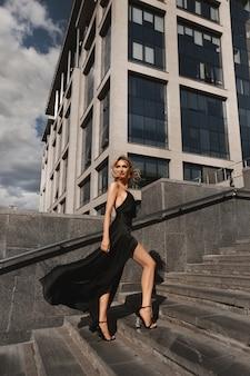 Belle fille blonde sexy et à la mode avec un corps parfait en robe de soirée noire posant au fond urbain