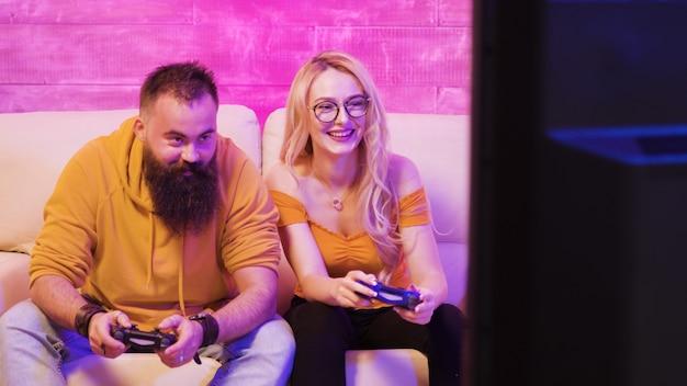 Belle fille blonde souriante en jouant à des jeux vidéo avec son petit ami à l'aide de contrôleurs sans fil sur un téléviseur grand écran