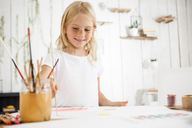 Belle fille blonde souriante et peindre joyeusement l'image avec un pinceau