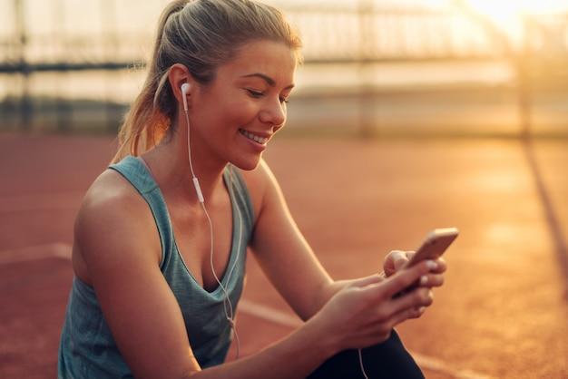 Belle fille blonde sportive souriante assise à l'extérieur avant de s'entraîner et d'écouter de la musique.