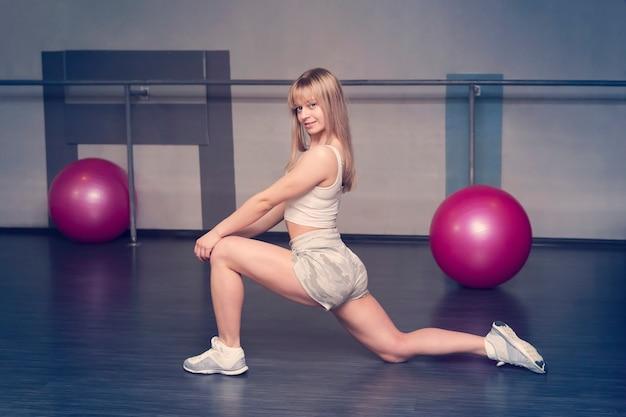 Belle fille blonde en tenue de sport fait des exercices, belle instructeur blonde souriante en short court et t-shirt blanc faisant des étirements dans la salle de gym sur fond de balles de gym roses