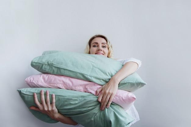 Belle fille blonde tient beaucoup d'oreillers dans ses mains. elle se couche dessus avec plaisir