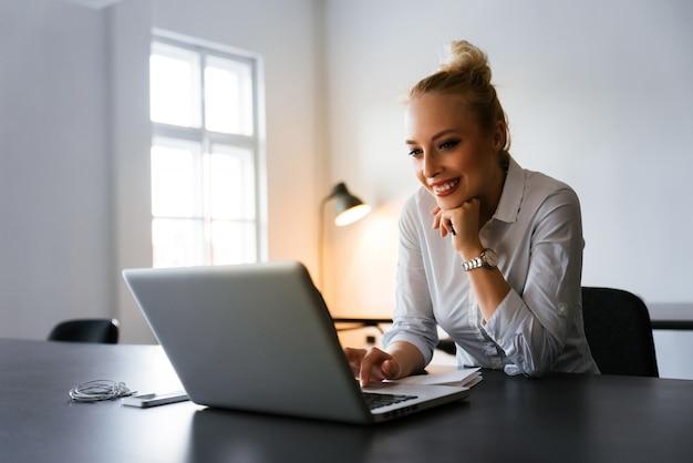 Belle fille blonde utilisant son ordinateur portable pour surfer sur le web