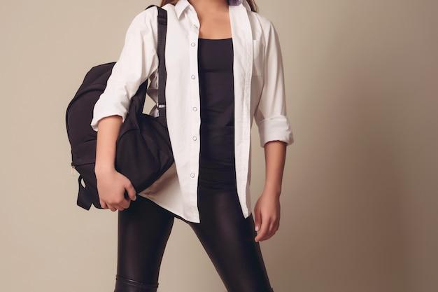 Belle fille blonde vêtue d'une chemise blanche avec un sac à dos en cuir sur le dos