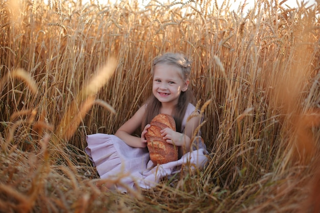 Une belle fille blonde vêtue d'une robe en lin rose est assise dans un champ de blé et mange du pain