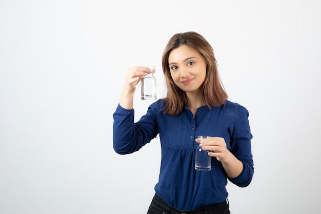 Belle fille en blouse bleue tenant un verre d'eau sur blanc.