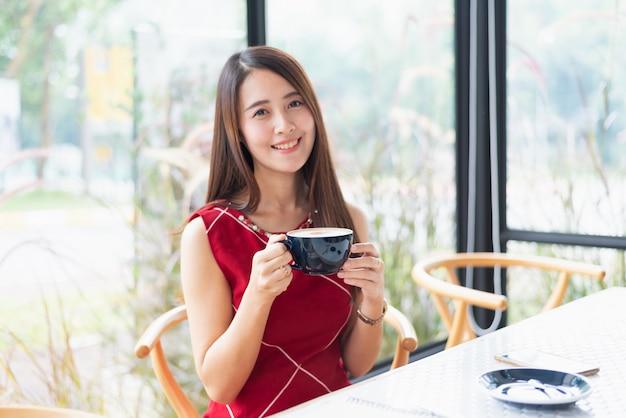 Belle fille boire un café chaud au café