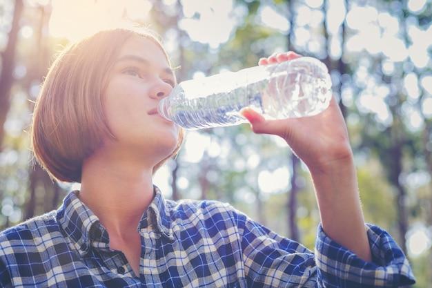 Belle fille boire de l'eau d'une bouteille en plastique avec le lever du soleil