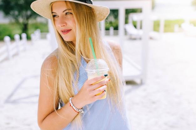 Belle fille boit du jus de fruits