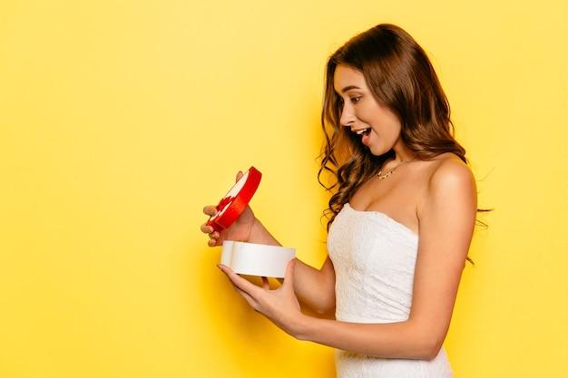 Belle fille avec boîte-cadeau d'ouverture de visage demandé, reçu de son petit ami