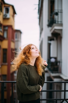 Belle fille bouclée aux cheveux roux dans un siter tricoté chaud sur le balcon regarde rêveusement le ciel