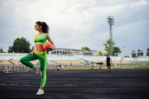 Belle fille bouclée, flexion des muscles dans le stade. réchauffez-vous avec le ballon. la fille fait du sport. survêtement vert clair.
