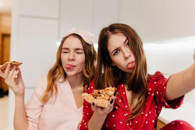 Belle fille bouclée en masque pour les yeux rose tenant une tranche de pizza. femme aux cheveux noirs en tenue rouge faisant selfie pendant le petit déjeuner.