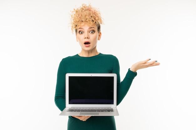 Belle fille bouclée tenant un ordinateur portable avec une maquette dans ses mains sur blanc